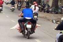 【写真3】皮を剥いだ豚をバイクで運ぶ